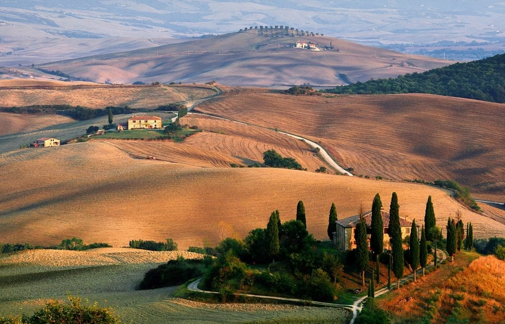 typical Tuscan countryside with farm house, narrow winding roads, and cypress trees - driving in Tuscany