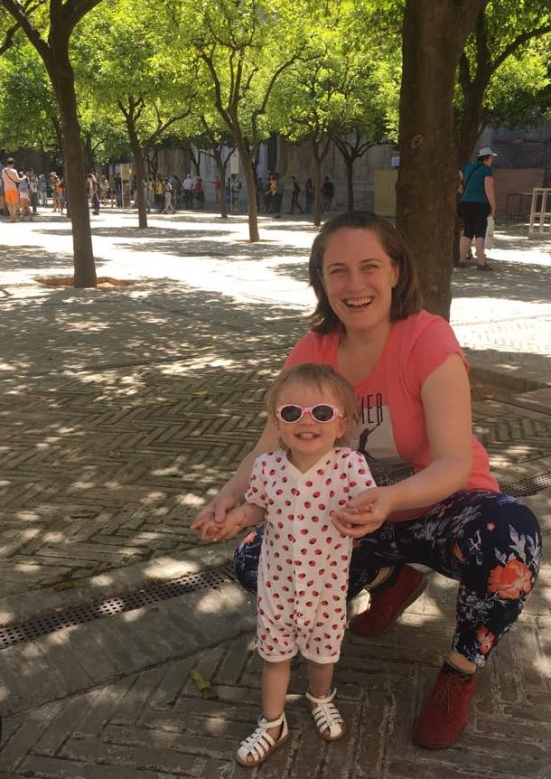Our toddler rying on her new sunglasses in the garden of Seville's Cathedral