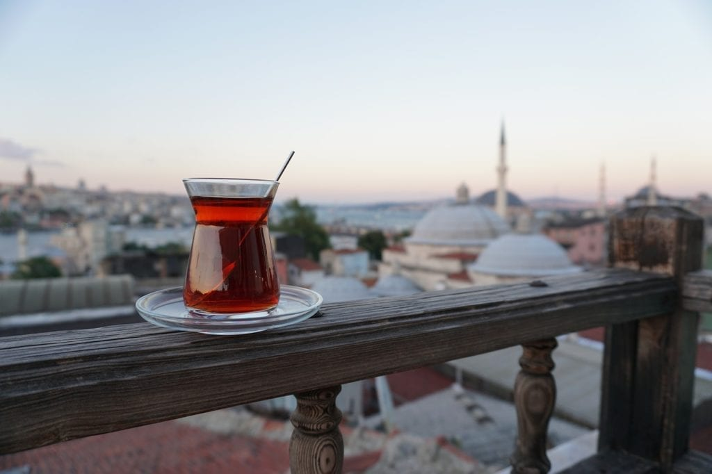 A glass of steaming Turkish tea is a must during winter in Istanbul - glass of tea with a view over the rooftops.