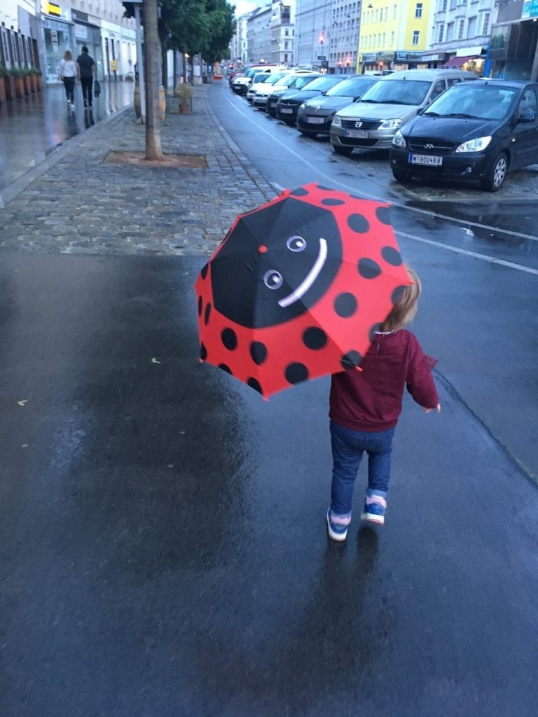 Vienna in 2020 - pandemic - toddler in the rain red umbrela